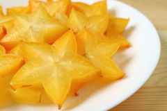 Closed up vibrant color fresh Star Fruit sliced in many pieces served on white plate Stock Photo