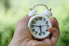 Closed up of white alarm clock in woman hand as business or time Stock Photo