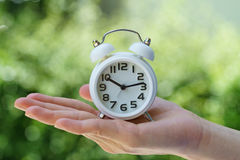 Closed up of white alarm clock in woman hand as business or time Royalty Free Stock Photos
