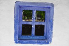 Closed vintage blue window on white wall of old house in romania.  Stock Photo
