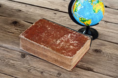 Closed vintage book with a globe on a wooden table close up Royalty Free Stock Photography