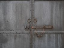 Closed vintage retro black rusty metallic iron doors with bolt and round handles.  royalty free stock photo