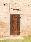Closed vintage wooden door on brick wall Royalty Free Stock Images