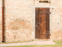 Closed vintage wooden door on brick wall Stock Photo