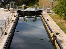 A closed water lock on a narrow channel in the woods. royalty free stock photo