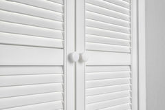 Closed White Door on grey Wall Stock Image