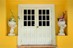 Closed white door on yellow wall. And have two flower vase with flowers in the front Royalty Free Stock Photography