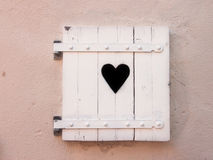 Closed white old shutters with heart shape (18). Closed white old shutters with heart shape on a colored wall Stock Image