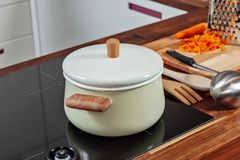 Closed white saucepan with wood pens on the black stove in the kitchen room. Cooking a soup, preparation. Closed white saucepan with wood pens on the black stove royalty free stock photos
