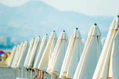Closed white umbrellas on the beach royalty free stock photography