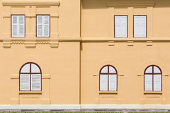 Closed white wooden windows on orange building Royalty Free Stock Photos