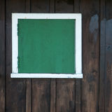 Closed window on a barn. A closed window with green shutters on a wooden barn Royalty Free Stock Photos