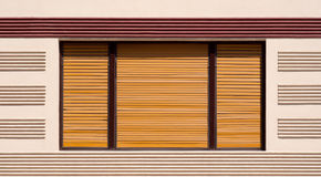 Closed window with brown wooden shutters Royalty Free Stock Photo