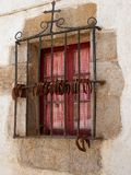 Closed window with iron grills and horseshoes. Basque Country. Square window made of stone with iron bars, an iron cross and horseshoes hanging on it. Basque Stock Photography
