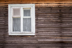 Closed window of the old log house made of wood. With curtains and net to protect them from insects stock image