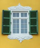 Closed window - open shutter. Arabesque window frame with open green shutter, yellow wall stock photos