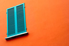 Closed window on orange wall Royalty Free Stock Photos