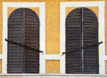 Closed windows with grates. Two old windows closed down with grates Royalty Free Stock Photo