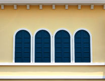 Closed windows on pale yellow wall Royalty Free Stock Photo