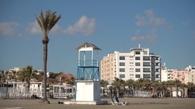 Empty closed for winter beach cafes during off-season. Beach umbrella`s sticks and lifeguard`s tower stock video footage