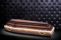 Closed wooden brown coffin covered with cloth  on gray luxury background. casket with shadow on background. Royalty Free Stock Photo