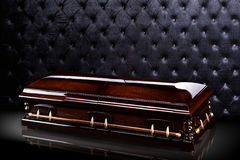 Closed wooden brown sarcophagus isolated on gray luxury background. casket, coffin on royal background. Royalty Free Stock Photo