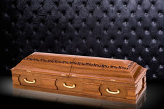 Closed wooden brown sarcophagus isolated on gray luxury background. casket, coffin on royal background. Stock Images