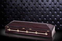 Closed wooden brown sarcophagus isolated on gray luxury background. casket, coffin on royal background. Royalty Free Stock Image