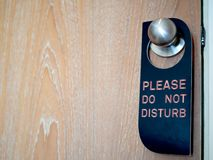 Closed wooden door of hotel room with please do not disturb sign hanging on the stainless steel door knob stock images