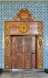 Closed wooden engraved aged door framed by golden ornate wooden frame on Turkish ceramic tiles wall with floral blue patterns Royalty Free Stock Photos