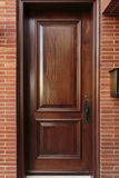 Closed Wooden Front Door of a Luxury Home. Closed wooden front door of an upscale home, with a black door handle, and framed by the brick house. Mailbox is also Stock Photos