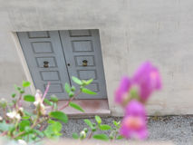 Closed wooden front door to a home with blurred flowers in foreground . View from above Royalty Free Stock Images