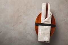 Closed wooden Japanese lunchbox with chopsticks, wrapped in a festive cloth on an old stone table. Top view with copy Royalty Free Stock Photo