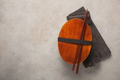 Closed wooden lunchbox with Japanese sticks on an old stone table. Top view with copy space Stock Image