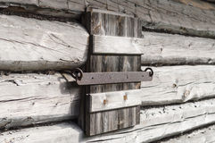 Closed wooden shutter on aged wall of log cabin Royalty Free Stock Images