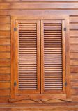 Closed wooden shutters on a wooden panneled wall Royalty Free Stock Photography