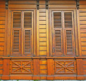 Closed wooden shutters on a wooden panneled wall Stock Photography
