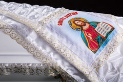 Closed wooden white coffin with white silk cloth with a picture of God. close-up on dark royal background. Christian funeral ritual Stock Images