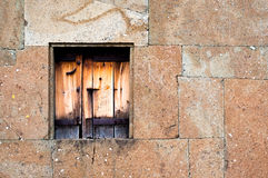 Closed wooden window in a stone wall Royalty Free Stock Photo