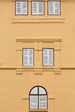 Closed wooden windows on orange building. Royalty Free Stock Photography
