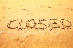 Closed written on sand on beach Royalty Free Stock Photo