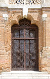 Closed wrought iron door on old brick wall. With details on the sides royalty free stock photos