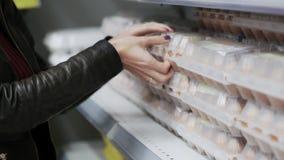 Closee вверх по рукам женщины покупает яйца, испытывает их Покупатель покупает упаковку яйца видеоматериал