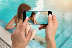 Closely image of female hands holding mobile phone with photo camera mode on the screen. Cropped image of beautiful long stock photo