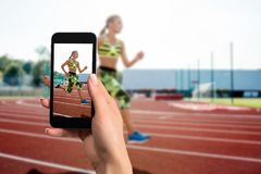 Closely image of female hands holding mobile phone with photo camera mode on the screen. Cropped image of running woman. royalty free stock photos