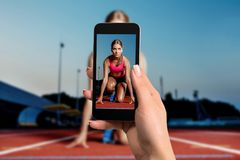 Closely image of female hands holding mobile phone with photo camera mode on the screen. Cropped image of running woman. royalty free stock photo
