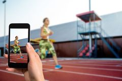 Closely image of female hands holding mobile phone with photo camera mode on the screen. Cropped image of running woman. stock photo