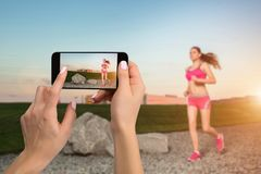 Closely image of female hands holding mobile phone with photo camera mode on the screen. Cropped image of running woman stock photos