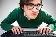 Closely looking at camera. Curious young man in green pullover and glasses using keyboard and closely looking at the camera Stock Photos