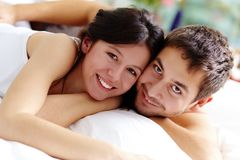 Closeness. Happy couple lying in bed and looking at camera with smiles Royalty Free Stock Photo